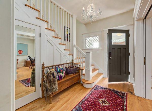 Яркие аксессуары, использованные в дизайне интерьера прихожей с лестницей, представлены на этом фото