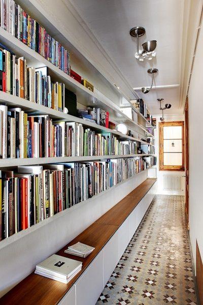 Узкий коридор, украшенный длинными книжными полками - отличный вариант для тех, кто собирает домашнюю библиотеку